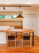 一続きになったキッチンカウンターとダイニングテーブルがある家