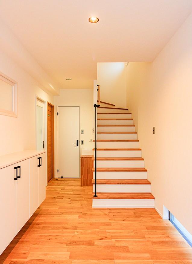 広い玄関と階段、花ブロックのある白の家