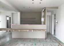 内部大工・クロス貼り完了。正面のキッチンカウンターとキッチン背面にポイントクロス、他は白色でシンプルな配色です。