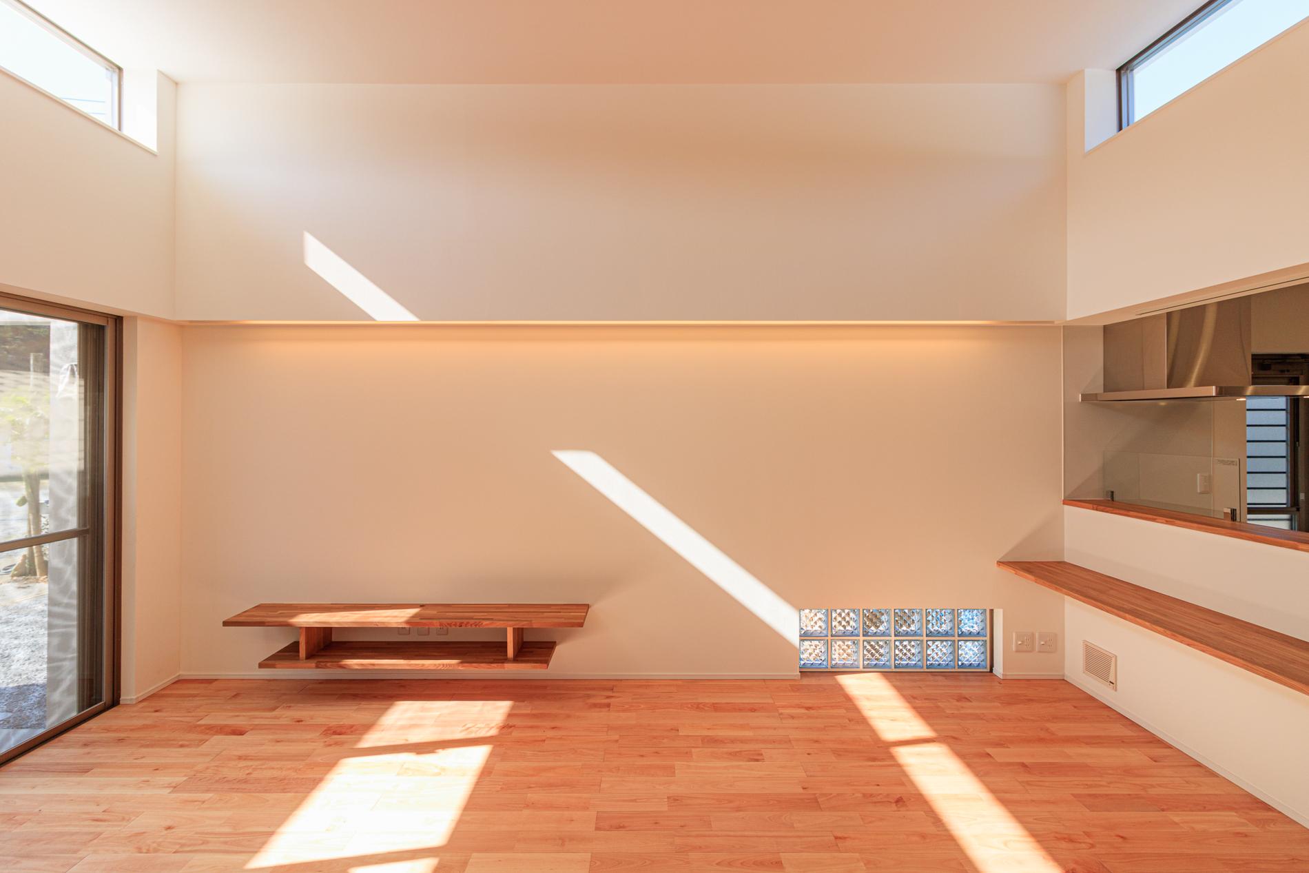 吹き抜けの高窓から光が降り注ぐ明るいLDKの子育てハウス
